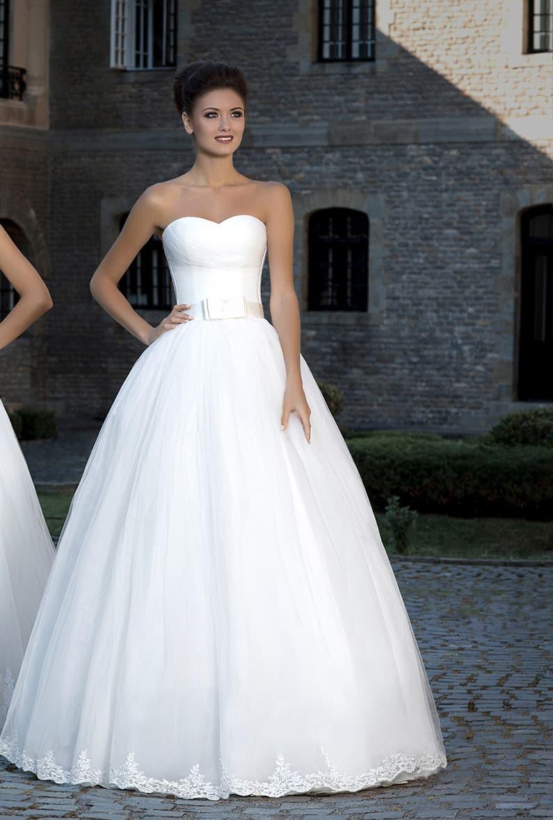 Классическое свадебное платье пышного кроя с открытым лифом и широким поясом с бантом.