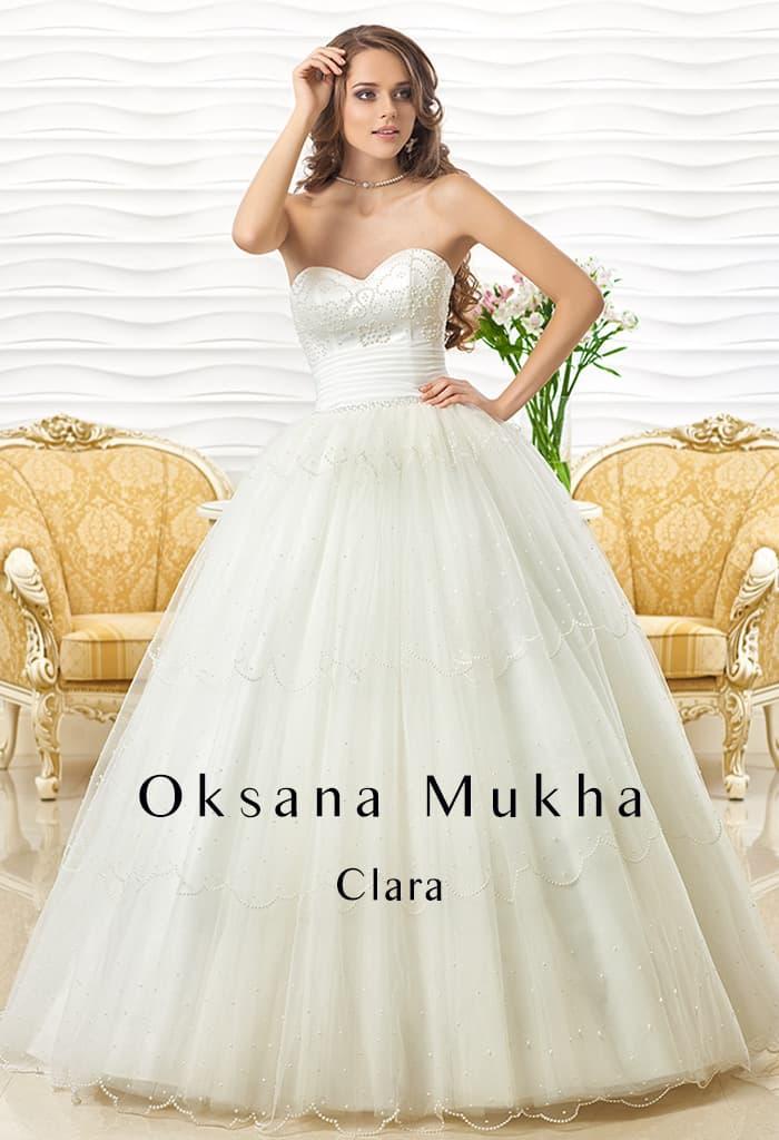 Свадебное платье с открытым корсетом, широким поясом и пышной юбкой.