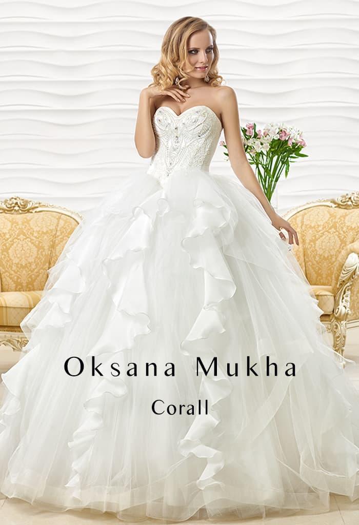 Свадебное платье с вышивкой на открытом корсете и отделкой из оборок по пышной юбке.