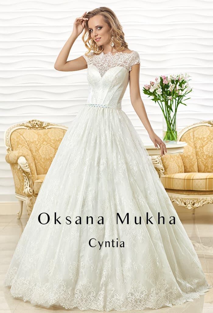 Кружевное свадебное платье с фигурным вырезом и многослойным подолом.