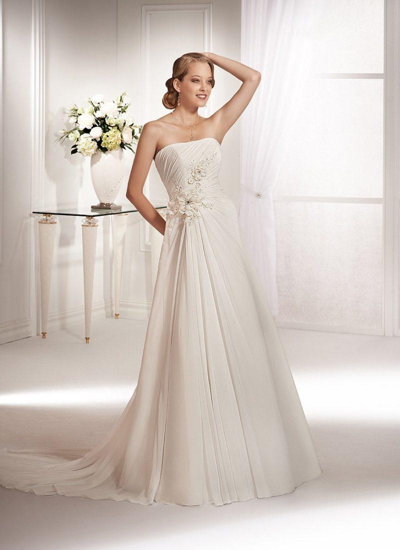 Элегантное свадебное платье с объемной отделкой корсета небольшими цветочными бутонами.
