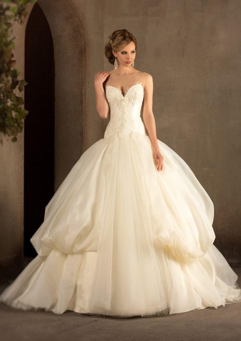 Пышное свадебное платье золотистого цвета с эксцентричной юбкой с объемными оборками по бокам.