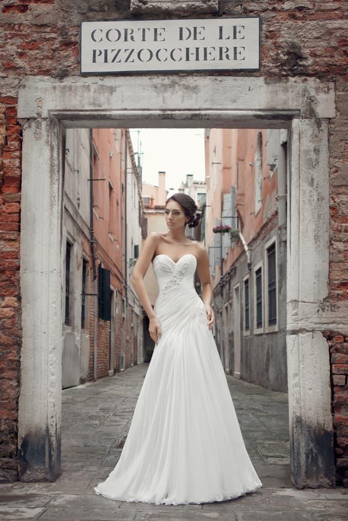 Деликатное свадебное платье в классическом стиле, украшенное вышивкой и драпировками.