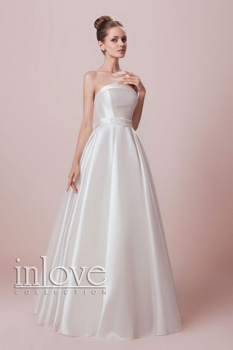 Впечатляющее свадебное платье с открытым лифом, выполненное из плотной глянцевой ткани.