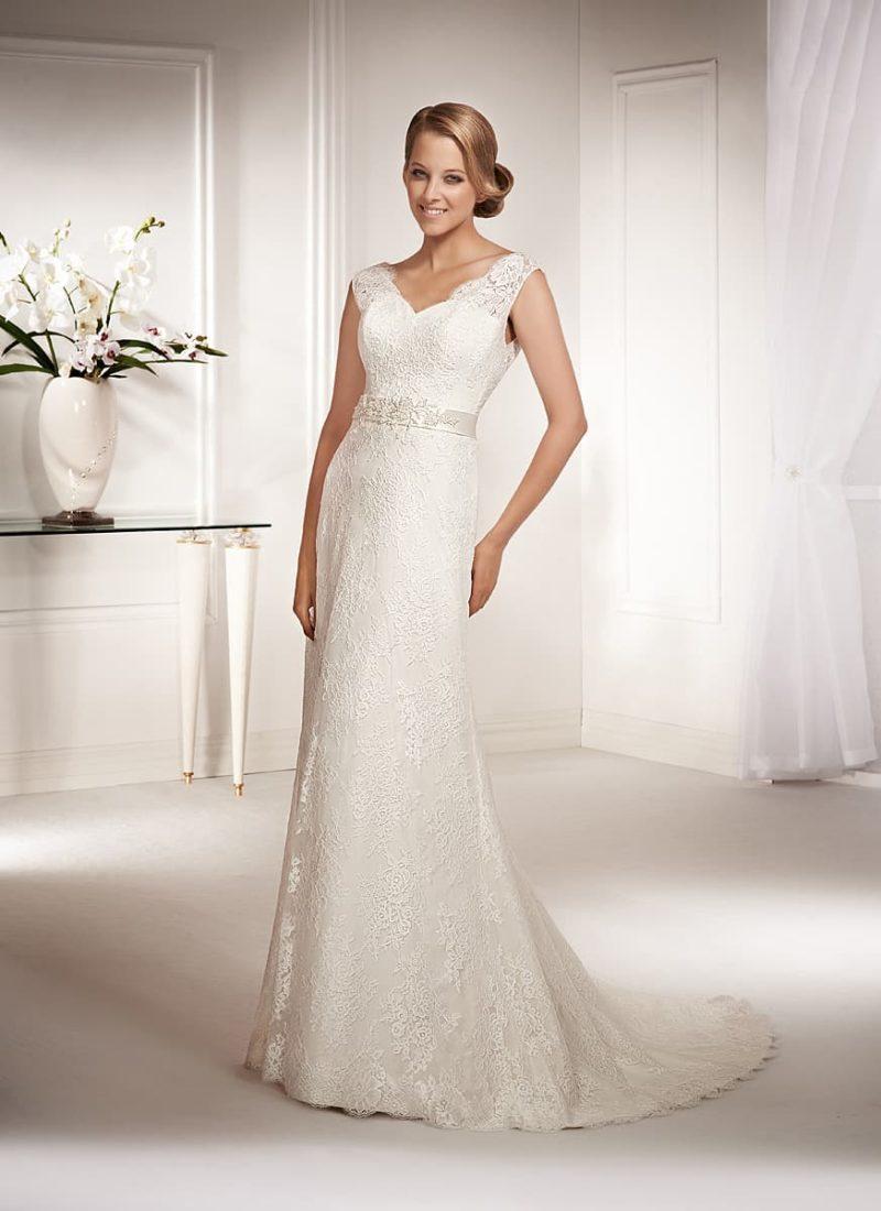 Лаконичное свадебное платье с кружевной отделкой и узким поясом на талии.