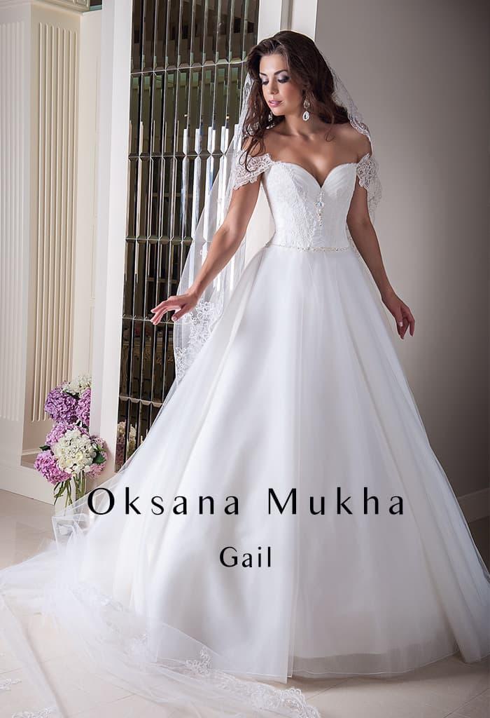 Открытое свадебное платье с притягательным декольте и многослойной юбкой.
