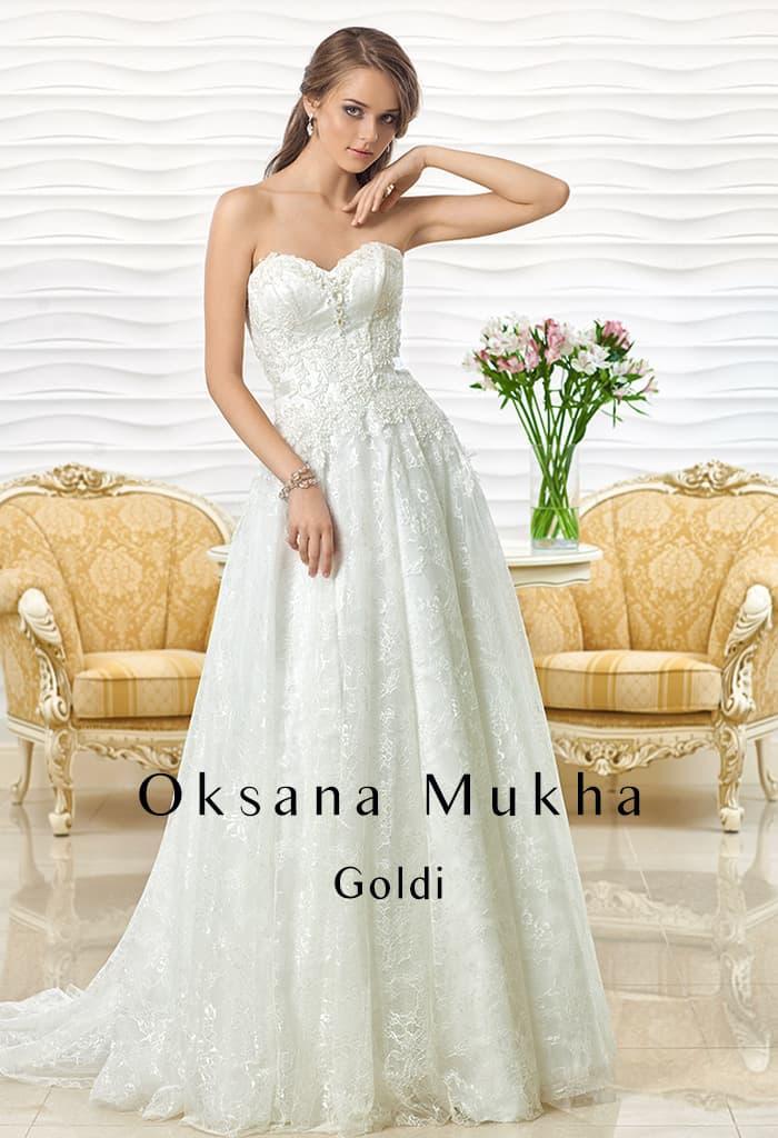 Фактурное свадебное платье с романтичным вырезом и многослойной юбкой.
