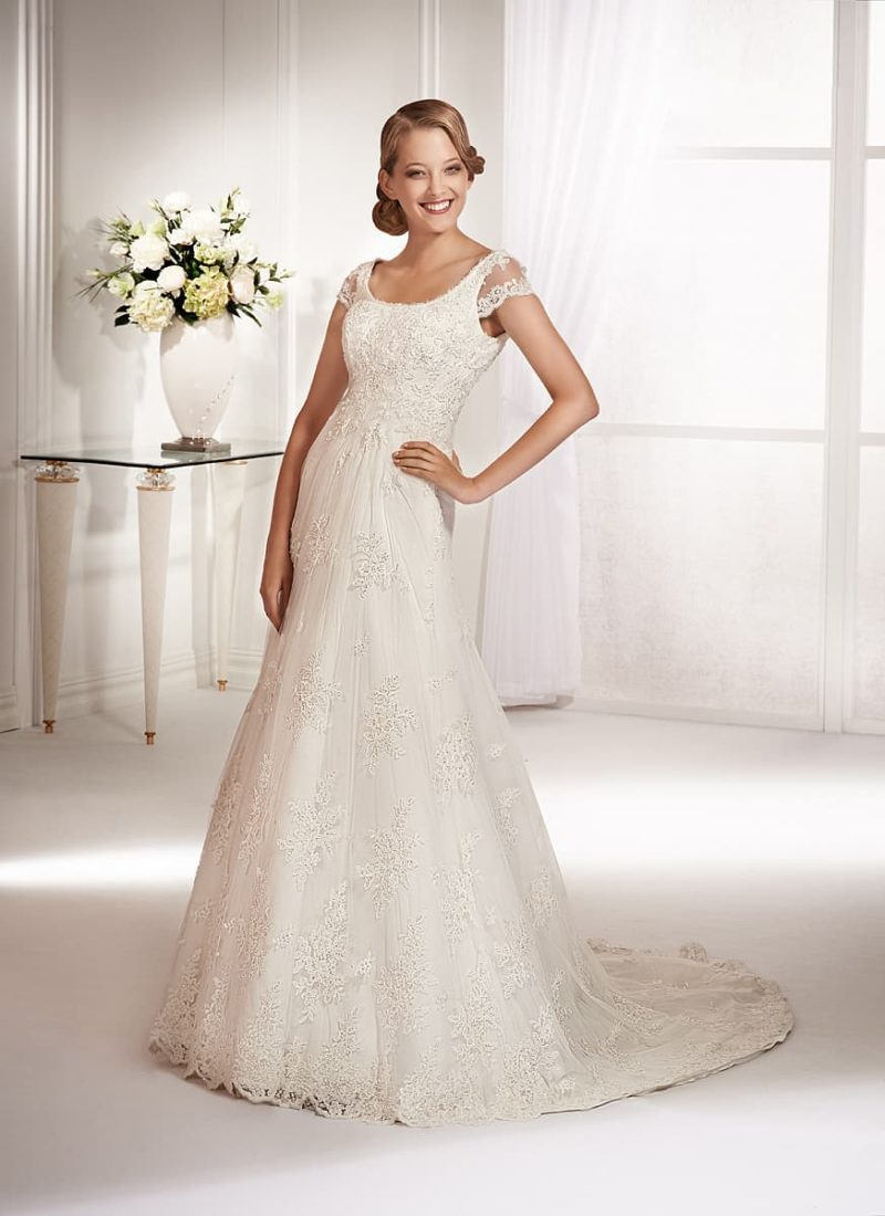 Стильное свадебное платье с округлым декольте и короткими прозрачными рукавами.