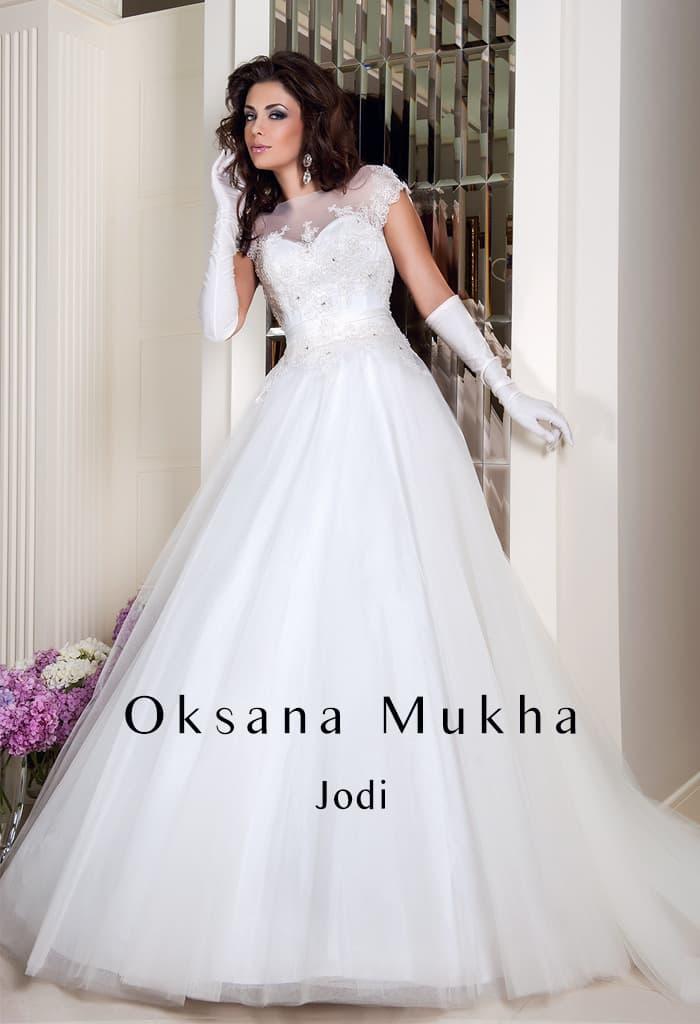 Роскошное свадебное платье пышного кроя с атласным корсетом и коротким рукавом.