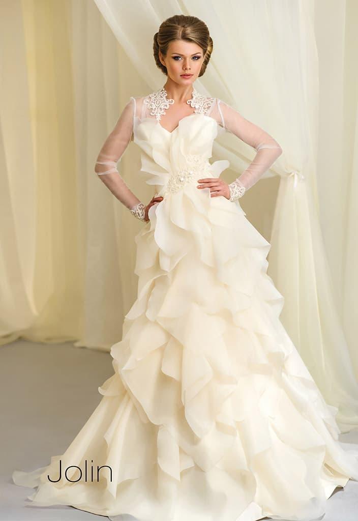 Свадебное платье кремового цвета, украшенное оборками по подолу.