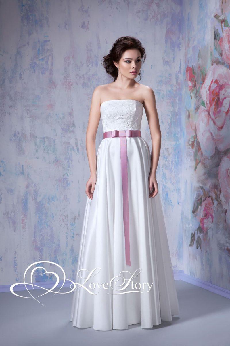 Атласное свадебное платье с сиреневым поясом и прямым декольте.