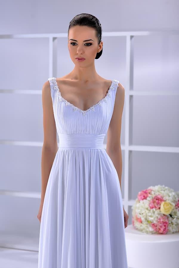 Изысканное свадебное платье с полупрозрачной юбкой прямого кроя и узкими бретелями.
