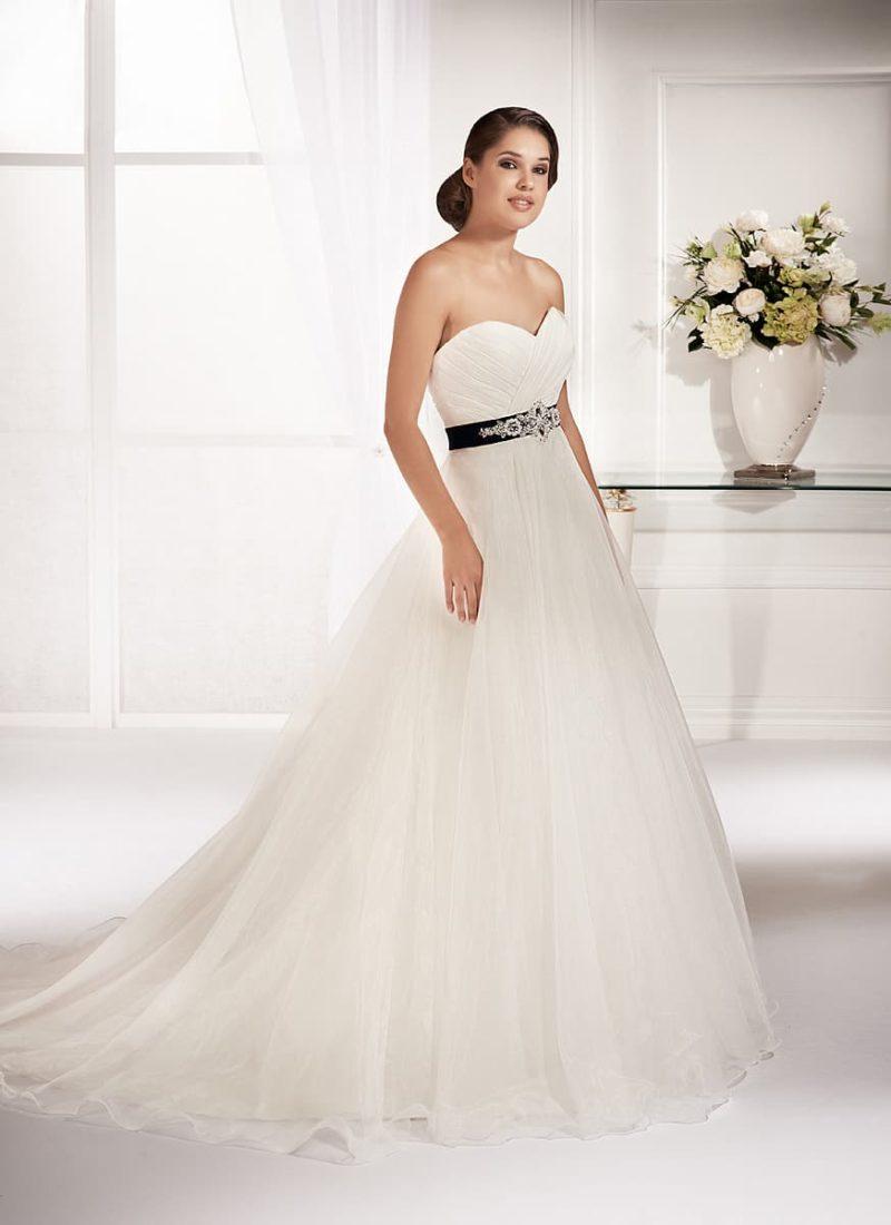 Романтичное свадебное платье пышного кроя с открытым лифом и цветным атласным поясом.