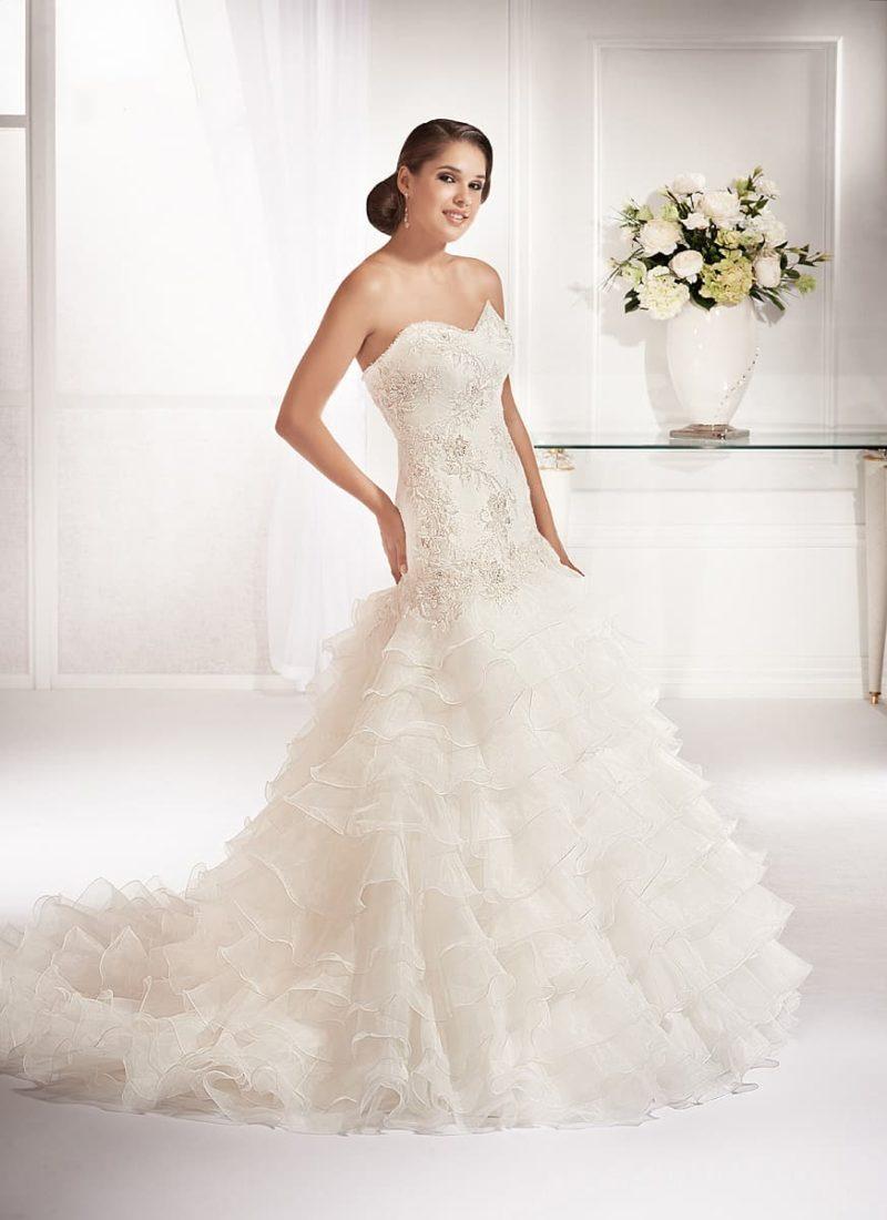 Свадебное платье «рыбка» с многоярусной юбкой со шлейфом и открытым лифом с вышивкой.