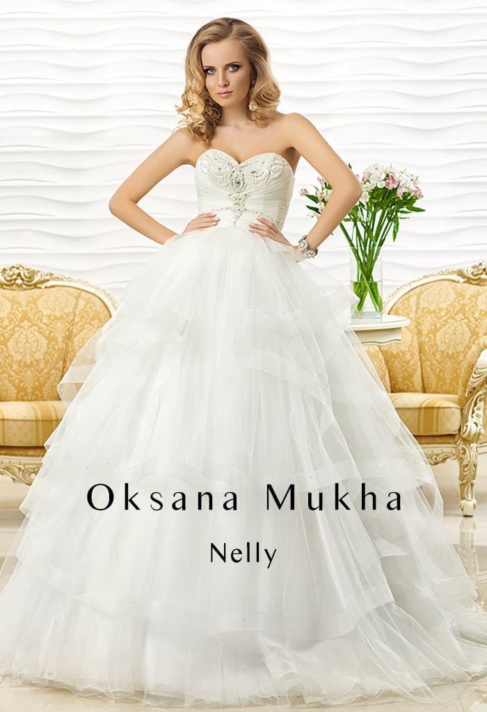 Свадебное платье с пышной юбкой из полупрозрачной ткани и открытым лифом с вышивкой.