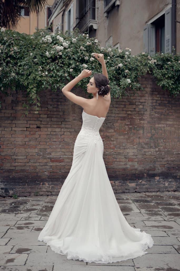 Открытое свадебное платье «рыбка» с многослойным шлейфом, спускающимся от уровня бедер.