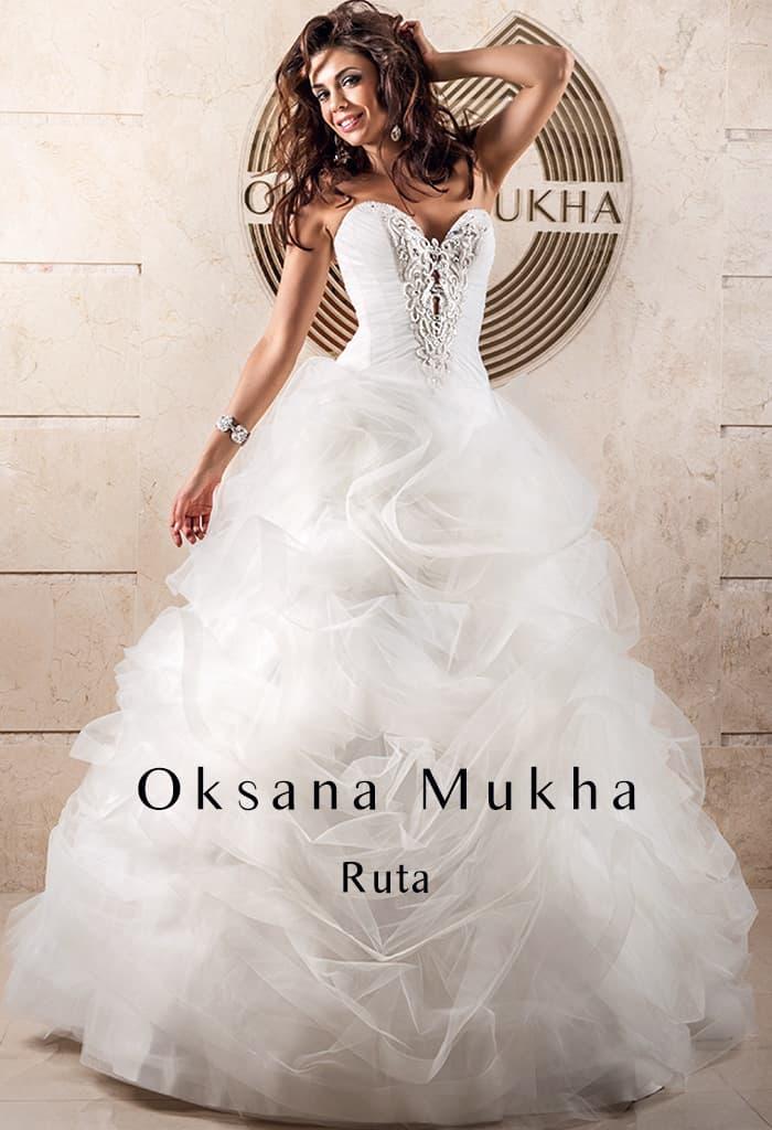 Открытое свадебное платье с выразительным декором корсета и пышными оборками на юбке.