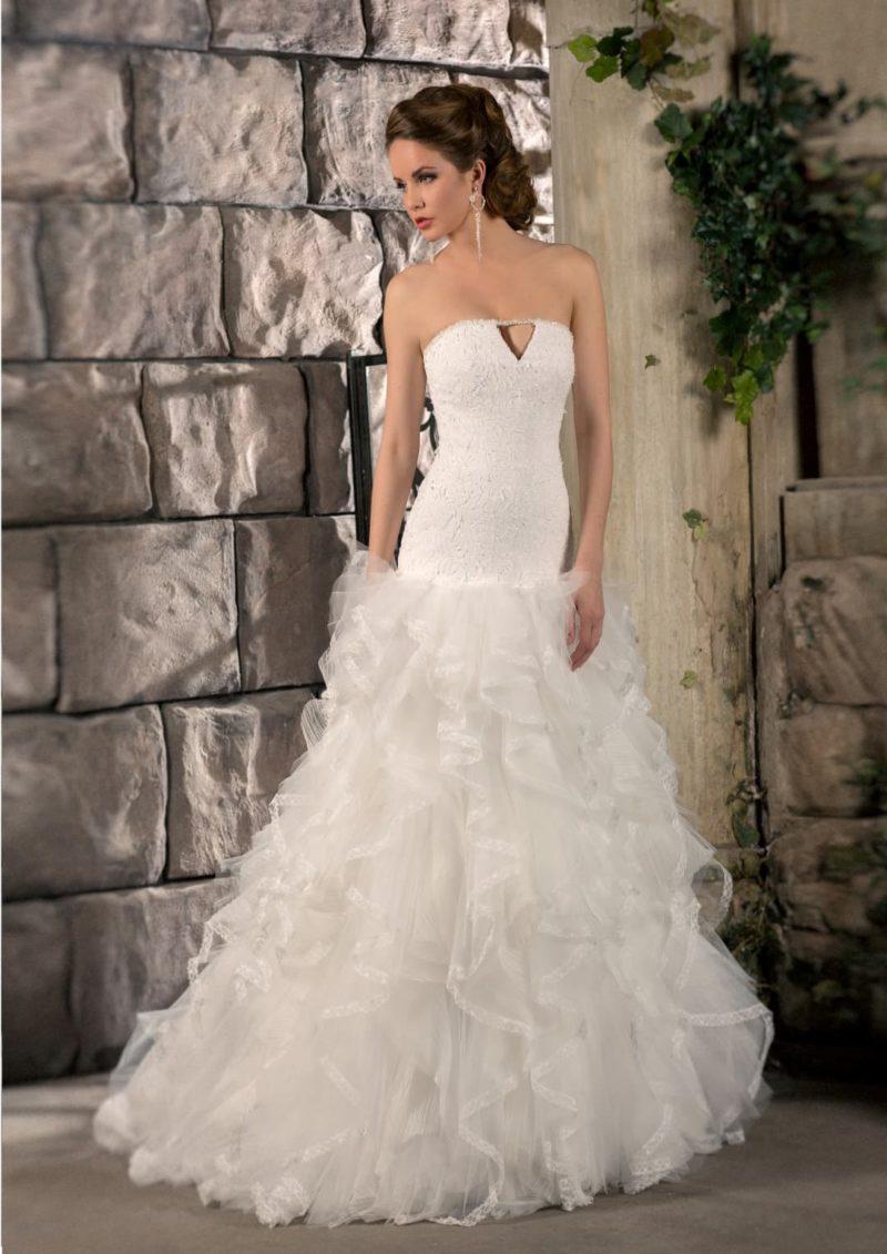 Притягательное свадебное платье с оборками по всей длине юбки и оригинальным вырезом лифа.