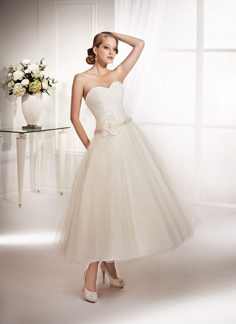 Свадебное платье чайной длины с заниженной линией талии, выделенной сияющим поясом.