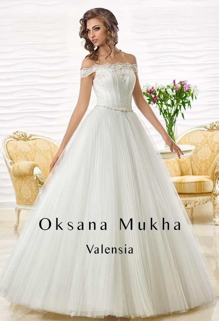 Впечатляющее свадебное платье с многослойной юбкой и портретным декольте.