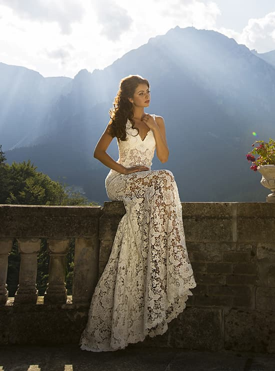 Свадебное платье с глубоким декольте и прямой юбкой, покрытой крупным кружевом.