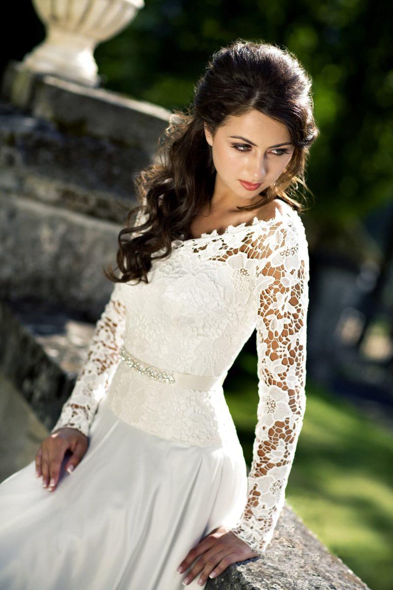 Свадебное платье с длинным рукавом из кружева с крупным рисунком и атласной пышной юбкой.