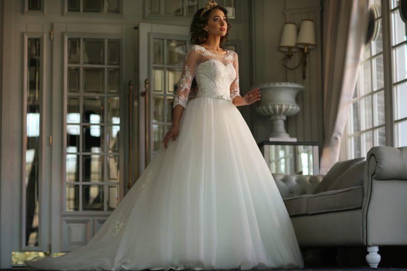 Безупречно красивое свадебное платье пышного кроя с фактурной отделкой изящного верха.