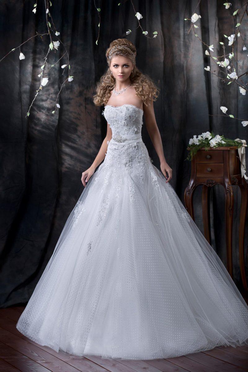 Свадебное платье с фактурным полупрозрачным верхом пышной юбки и открытым корсетом.