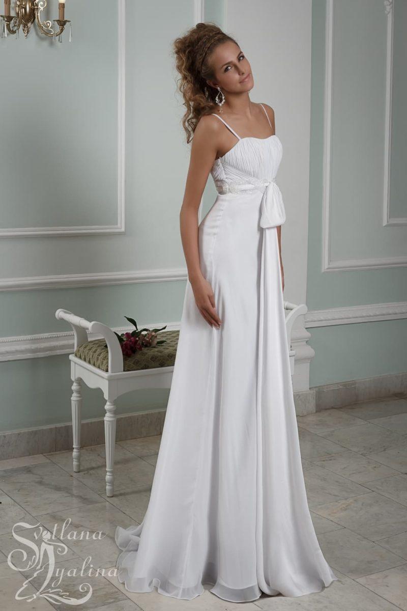 Прямое свадебное платье с завышенной талией, выделенной поясом с бантом.