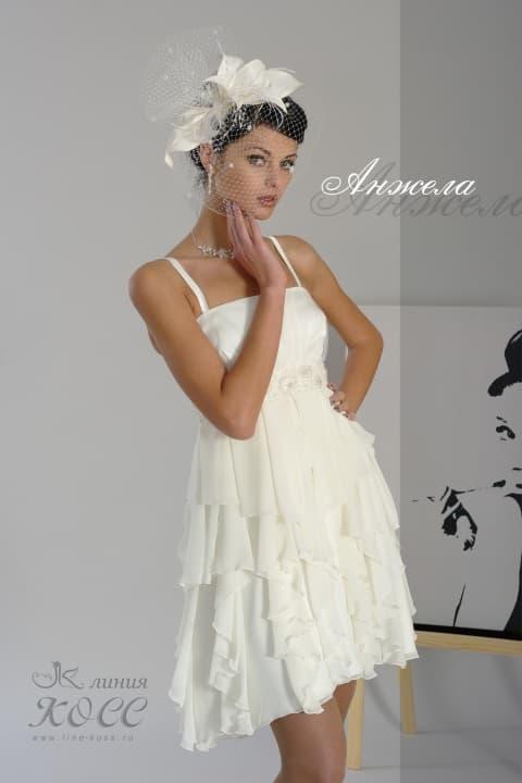 Короткое свадебное платье с оборками на юбке и открытым лифом с бретелями.