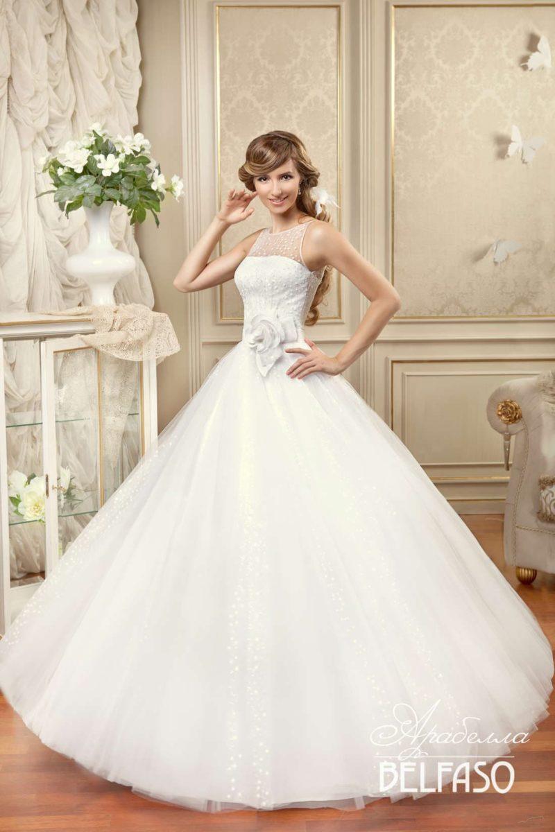 Изысканное свадебное платье пышного кроя с сияющей юбкой и крупным бутоном на уровне талии.