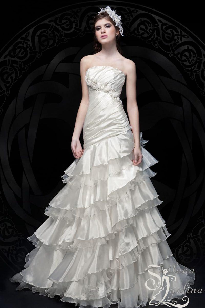 Глянцевое свадебное платье с оборками по юбке и прямым декольте.