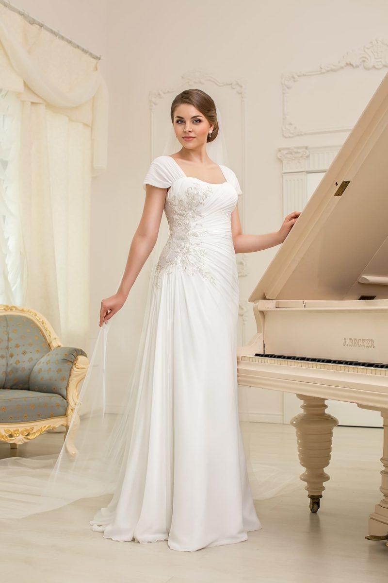 Романтичное свадебное платье с короткими рукавами и драпировками, облегающее фигуру прямым кроем.