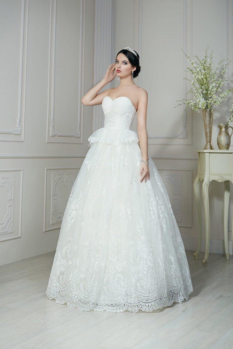 Пышное свадебное платье с кокетливой баской на талии и кружевными аппликациями по подолу.