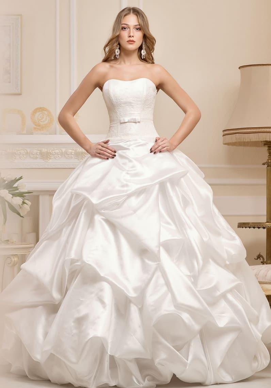 Драматичное свадебное платье с открытым лифом и причудливыми складками ткани по подолу.