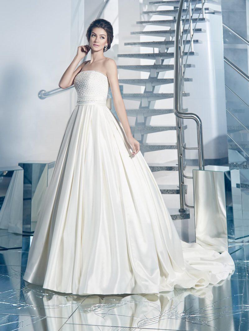 Великолепное свадебное платье с лифом прямого кроя и юбкой с вертикальными складками.