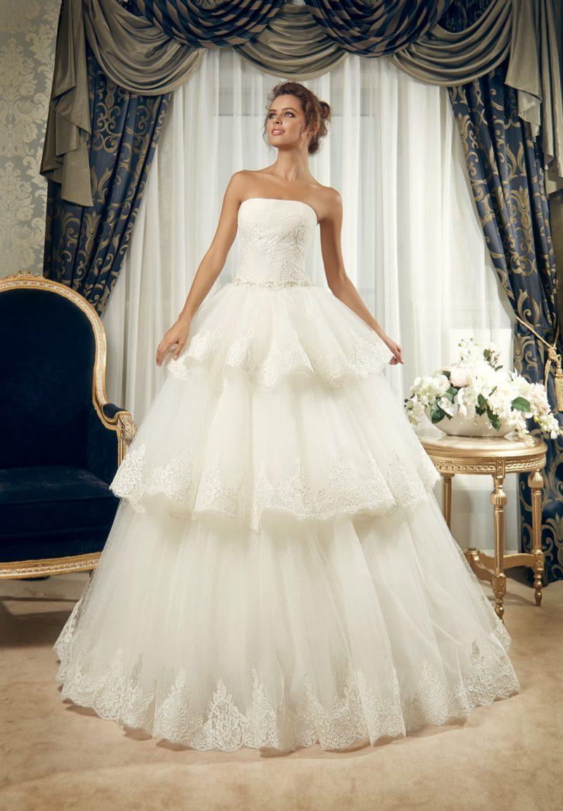 Открытое свадебное платье с деликатным лифом и многоярусной кружевной юбкой.