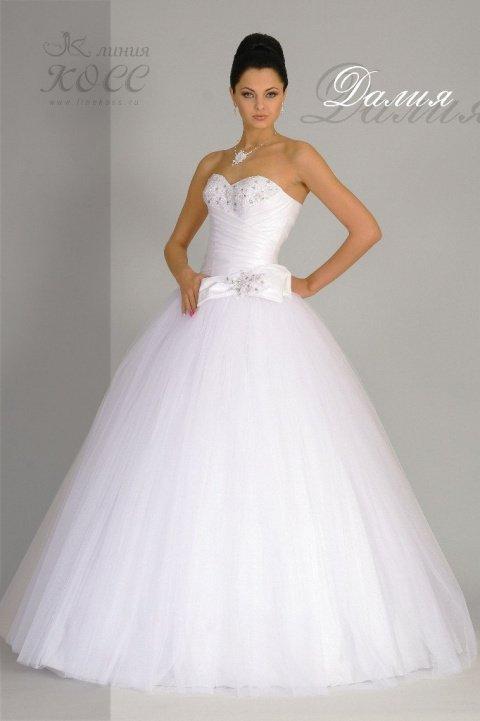Торжественное свадебное платье с вышивкой на лифе и бантом над пышной юбкой.