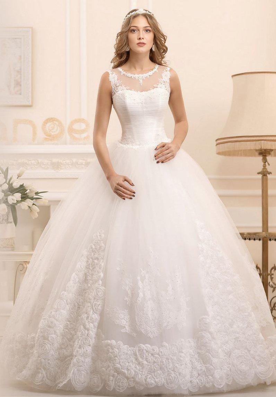 Классическое свадебное платье с многослойным низом и полупрозрачной вставкой над корсетом.
