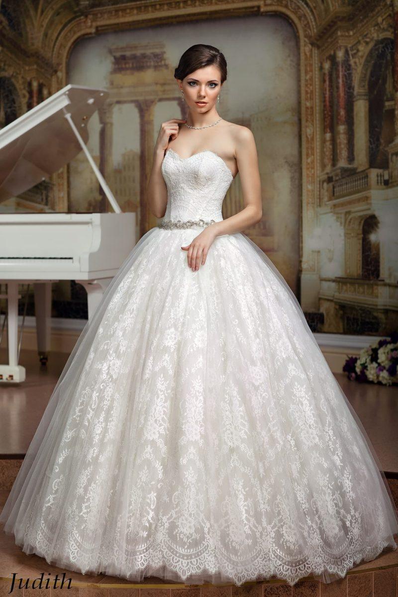 Потрясающее свадебное платье с открытым лифом и кружевной отделкой, а также узким поясом.