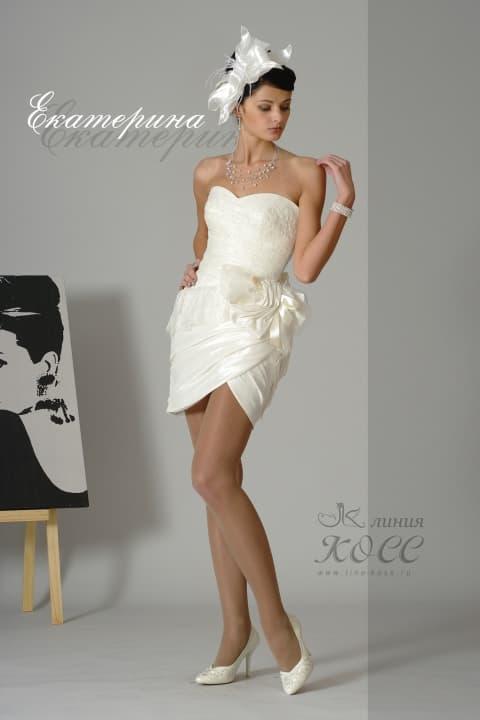 Открытое свадебное платье с юбкой до середины бедра и объемным декором.