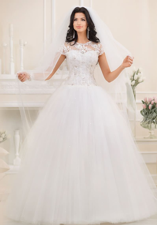 Роскошное свадебное платье с многослойным подолом и кружевным закрытым верхом с коротким рукавом.