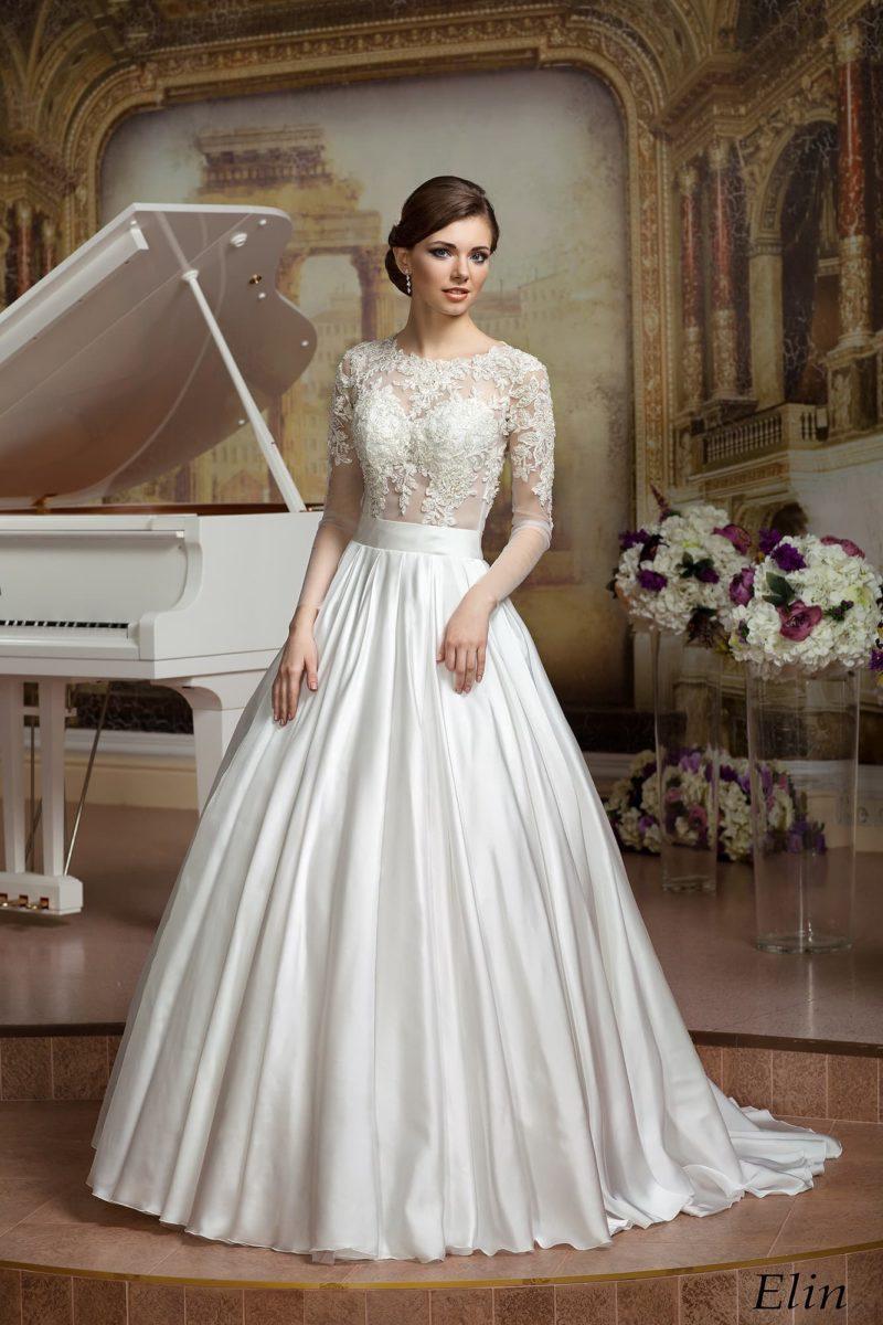 Пышное свадебное платье с атласной юбкой и полупрозрачным кружевным верхом с рукавами.