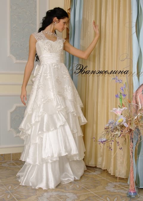 Свадебное платье с глянцевыми оборками по юбке и широкими кружевными бретелями.