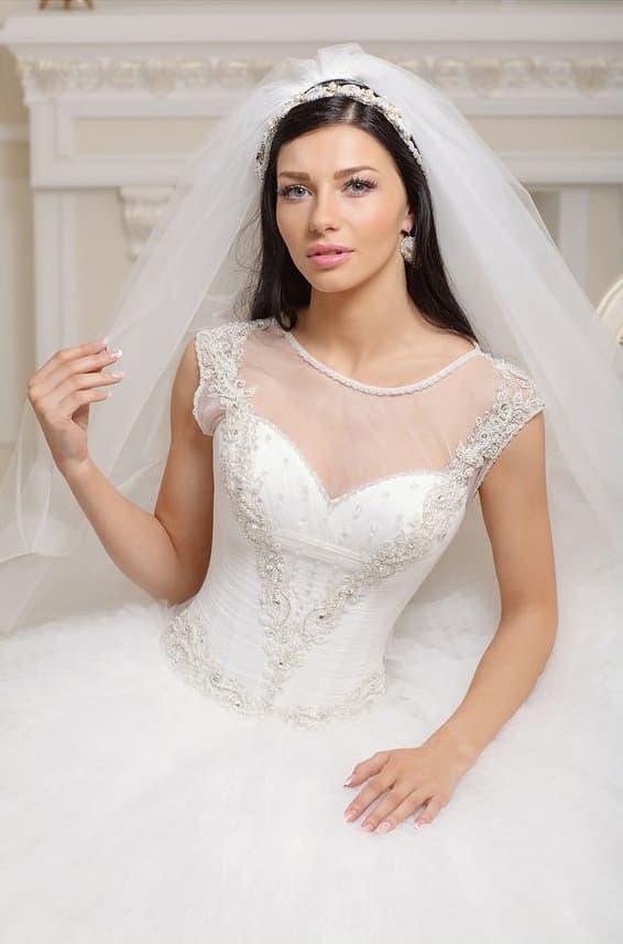 Свадебное платье с облегающим корсетом, украшенным серебристым бисером, и пышным силуэтом.