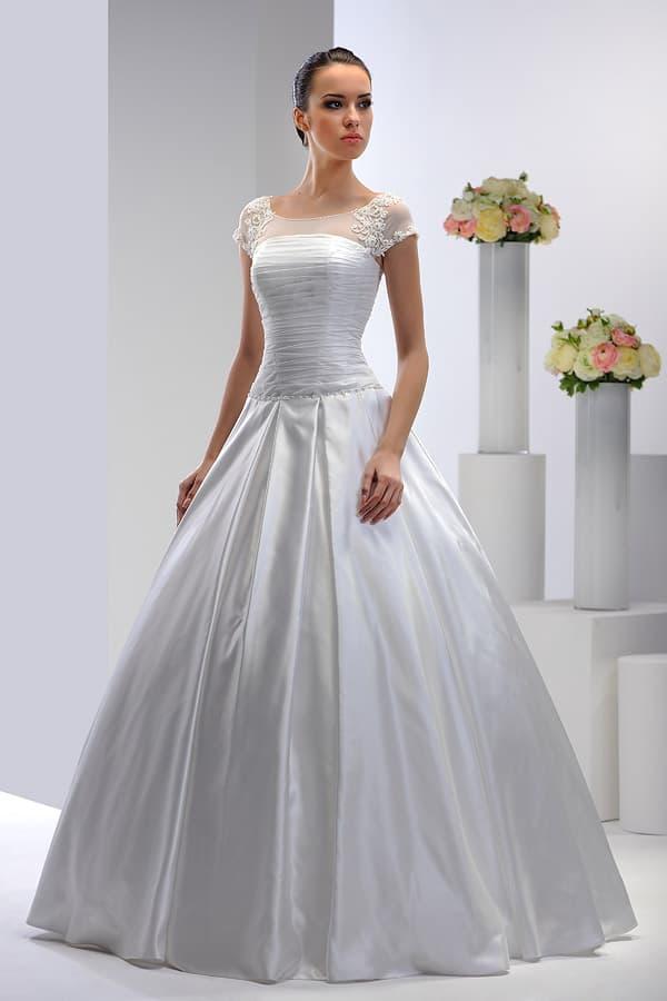 Свадебное платье из роскошной глянцевой ткани с тонким полупрозрачным верхом.