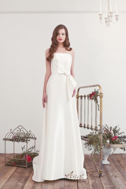 Открытое свадебное платье с лифом прямого кроя и пышным бантом на талии.