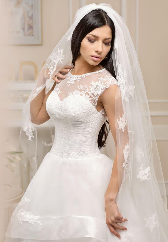 Пышное свадебное платье с кружевной вставкой над открытым корсетом и элегантной юбкой.