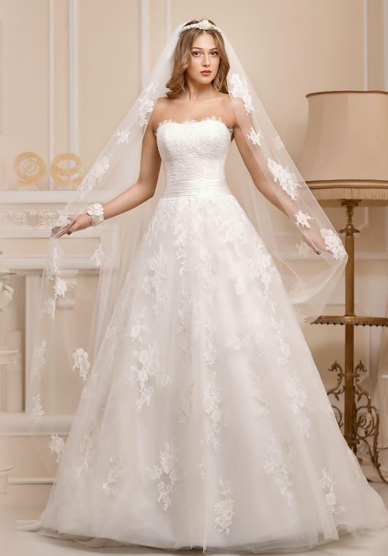 Открытое свадебное платье с лаконичным вырезом декольте и многослойной кружевной юбкой.