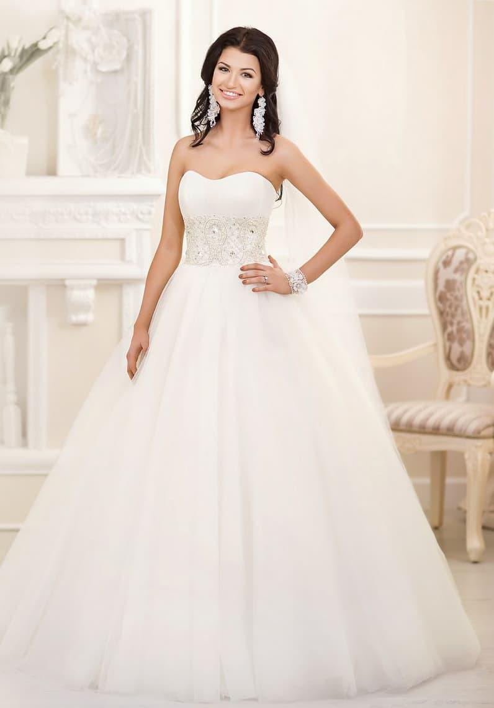 Роскошное свадебное платье с деликатной линией выреза и широкой полосой вышивки на талии.